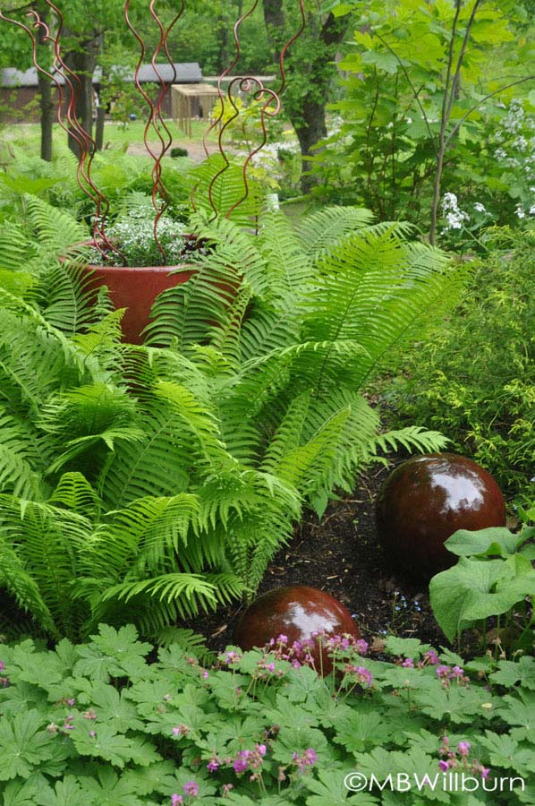 Red ceramic spheres paired with a red ceramic pot planted with painted tomato spirals and surrounded by ferns completely disguise the fact that the whole thing is covering an incredibly ugly well head.