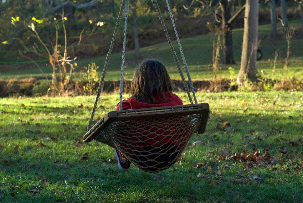 child sitting in swing